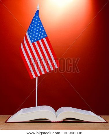 American flag on the stand and book on wooden table on red background