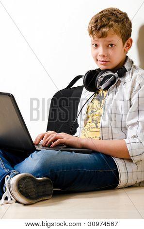 muchacho adolescente está sentado con el portátil en la escuela