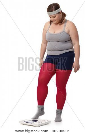 Fat woman in sportswear stepping on scale with fear.