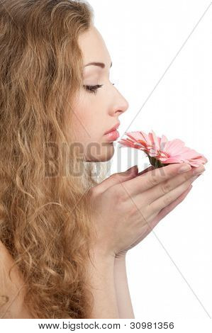 Young beautiful woman with healthy skin and long curly hair holding pink flower in her hands. Isolated on white background