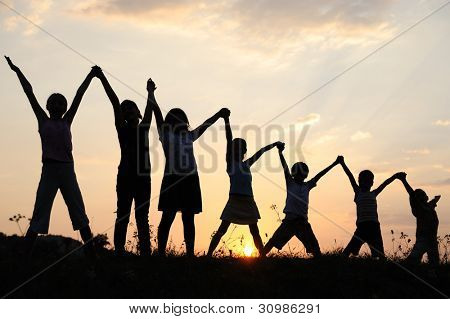 Several children generations with arms up in nature