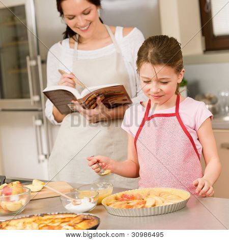 Mother and daughter making apple pie follow recipe from cookbook