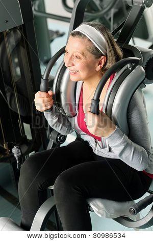 Fitness center senior woman exercise smiling on gym machine