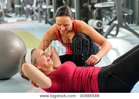Fitness center senior woman exercise with personal trainer on mat