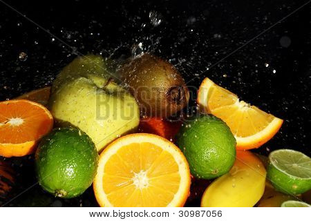 Fresh fruits and water splashes over black background