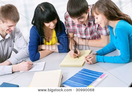 Group of students studying together in classroom