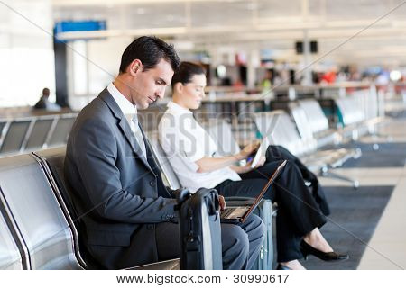 businessman and businesswoman using laptop and tablet computer at airport
