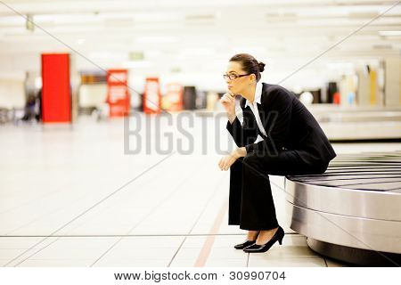 businesswoman sitting on conveyor belt and waiting for her luggage at airport