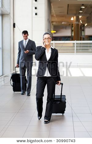 businesspeople walking in airport with luggage