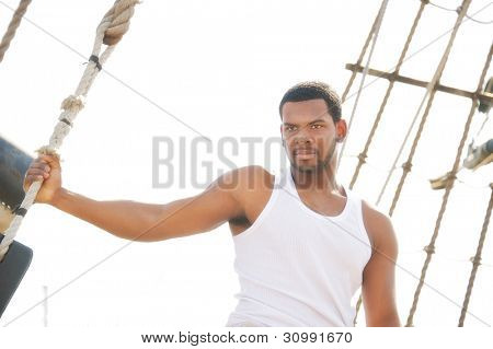 Handsome afro-american man on boat's deck.