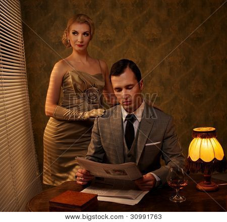 Man in suit reading newspaper with woman behind him.