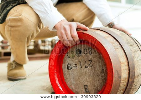 A brewer in his brewery is loading a beer barrel