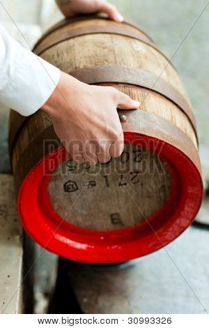 brewer in his brewery is traditionally sealing a beer barrel with tar pitch