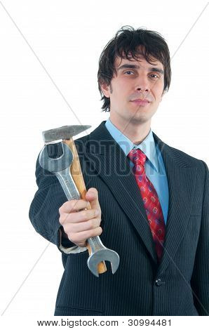 Elegant smiling businessman handing out hammer and wrench isolated on white