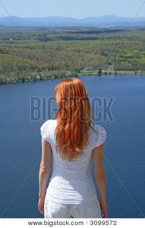 Red-Haired Girl Looking Over Blue Lake