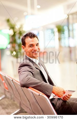 handsome young businessman using tablet computer at airport