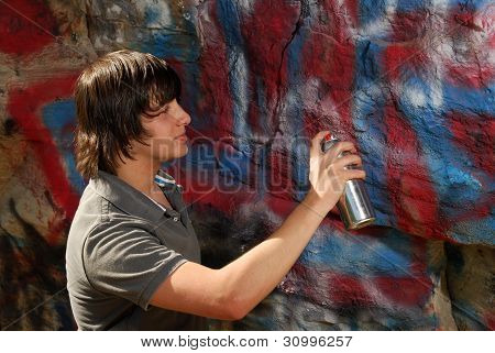 Teenager Spray Painting A Rock
