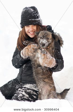 Pretty teenage girl plays with her dog in thick snow