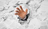 stock photo of sos  - Hand reaches out from big heap of crumpled papers - JPG