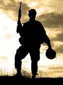 stock photo of soldiers  - Silhouette of US soldier with rifle against a sunset - JPG