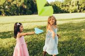 Two Little Girls Playing With A Paper Plane In Summer Day In Park. Cute Kids Throwing Airplanes Outd poster