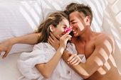 Cheerful Young Couple In Love Lying In White Bed, Enjoying Honeymoon In Sunny Morning. Smiling Hands poster