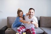Cheerful Young Beautiful Love Couple Fighting For Tv Remote While Sitting On The Sofa In Living Room poster