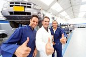 stock photo of thumbs-up  - Happy group of mechanics with thumbs up at a car garage - JPG