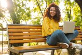 Photo of a pleased cheerful young beautiful curly student girl sitting outdoors in nature park using poster