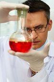 Serious clinician gazing at flask with red liquid in laboratory poster