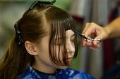 Hairdresser Making A Hair Style To Cute Little Girl. The Girl Cuts Off The Bangs. Work Hairdresser.  poster
