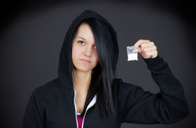 stock photo of methadone  - Gloomy portrait of a young woman or teen addict looking sad showing her little bag of drugs. ** Note: Slight blurriness, best at smaller sizes - JPG