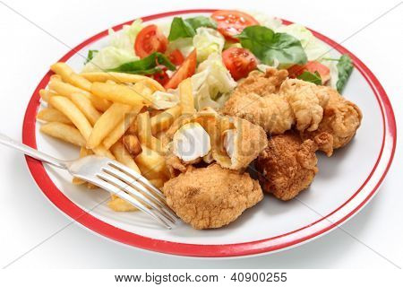 A meal of homemade kingfish nuggets served with french fried potato chips and a salad of tomato, lettuce and rocket, with a fork