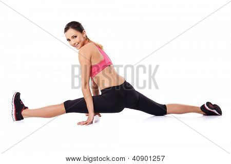Pretty smiling woman doing the splits to improve suppleness during a workout, studio portrait on white