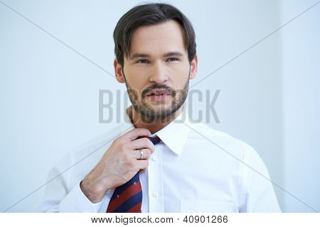 Bearded young man in shirtsleeves standing fiddling with the knot of his tie, head and shoulders studio portrait