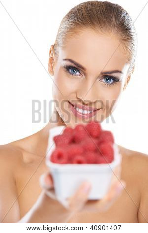 Beautiful smiling blonde woman with punnet of fresh ripe raspberries with focus to her blue eyes