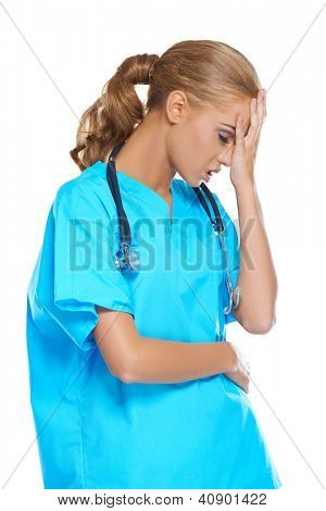 Attractive young female nurse or doctor dressed in scrubs with a stethoscope holding her hand to her head in anguish