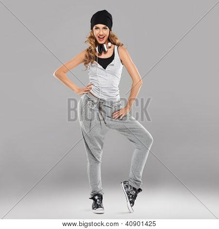 Vivacious beautiful young student in casual track pants and a cap with a set of headphones aound her neck laughing at the camera