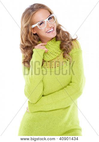 Vivacious beautiful woman with curly long blonde hair wearing modern white framed glasses and a warm winter jumper isolated on white