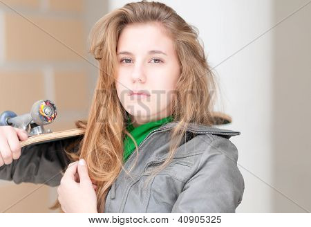 Portrait of pretty girl with skateboard outdoor.