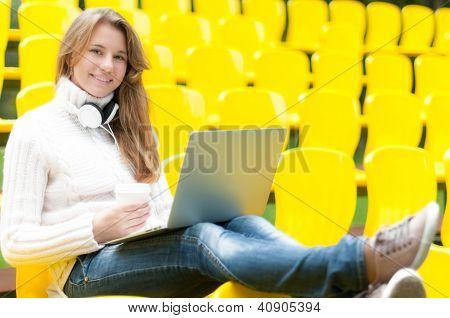 Young female student having break outdoor.