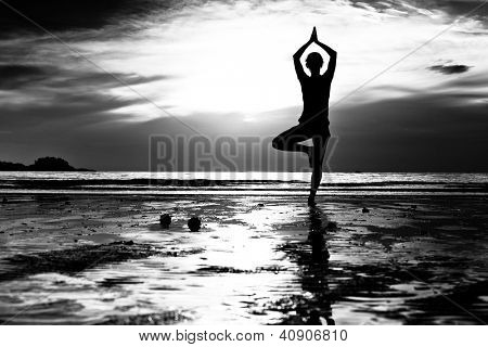 Black and white picture: Young woman practicing yoga on the beach at sunset.