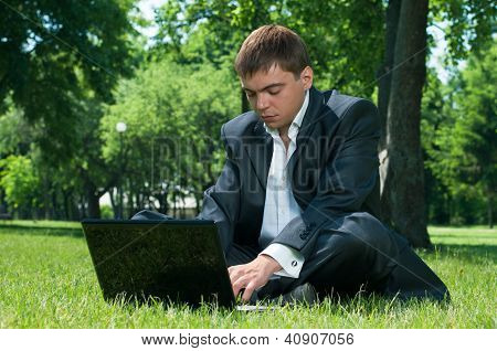 Business Man Sleeping On The Job At A Laptop On The Grass