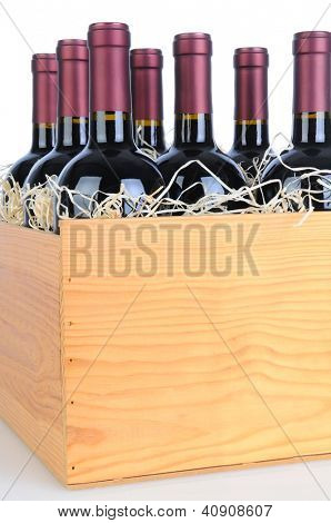Cabernet Sauvignon wine bottles in a wooden crate. Vertical format isolated on white with reflection.