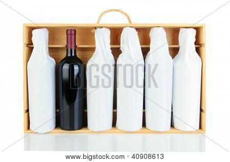 Six tissue wrapped wine bottles in a wooden crate with rope handle. Horizontal format isolated on white with reflection. One bottle is not wrapped.