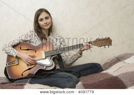 Attractive Young Woman Playing Guitar On Grey Background