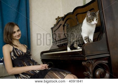 Young Woman Is Watching Cat Walking On Piano