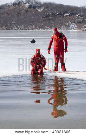 SPARTA, NJ - FEB 20: Two members of the Sparta Volunteer Fire Dept in orange immersion suits near an opening in the ice on Lake Mohawk during a charity plunge event on February 20, 2011.