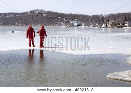 SPARTA, NJ - FEB 20: Two members of the Sparta Volunteer Fire Dept in orange immersion suits stand near an opening in the ice on Lake Mohawk during a charity plunge event on February 20, 2011.