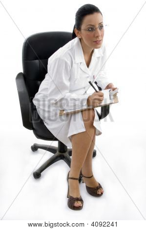 Side Pose Of Sitting Doctor With Writing Pad On White Background